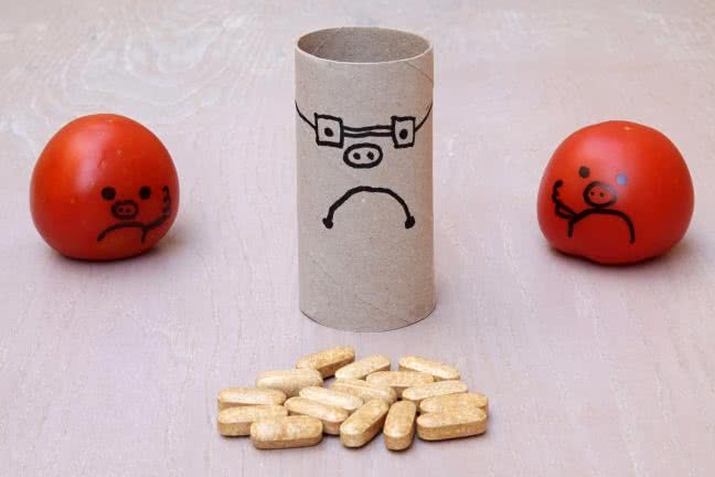 Group of sad smiley faces watching a heap of pills - free stock photo